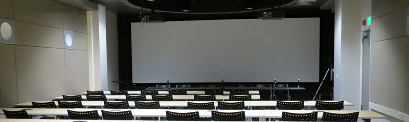 Image of the IDRE Portal with a set-up of chairs and a large screen at the front of the room.