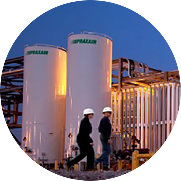 Image of two men in hardhats walking in front of Praxair plant